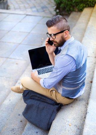 Photo pour Homme d'affaires moderne hipster assis dans les escaliers et utilisant un ordinateur portable et de prendre un appel sur un téléphone mobile. Jeune homme travaillant en plein air - image libre de droit