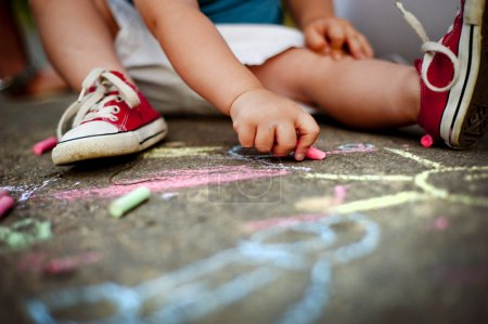 Photo for Close up of little boy in canvas shoes drawing with chalks on the sidewalk - Royalty Free Image