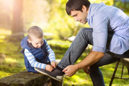 Little boy is tying his father's shoes