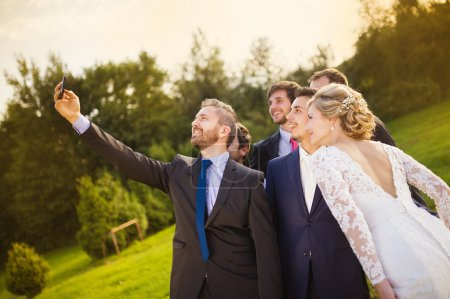 Bride, groom and his friends taking selfie