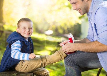 Photo pour Père aide son fils à nouer ses chaussures en été nature - image libre de droit