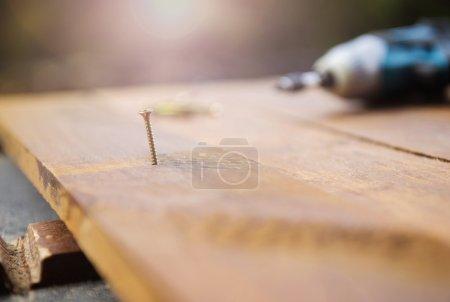 Photo pour Fermer perceuse électrique et clou gauche sur le sol en bois - image libre de droit