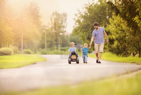 Father with his two little sons have fun on road