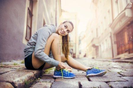 Female runner is tying her running shoes