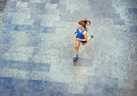 Female runner jogging on tiled pavement