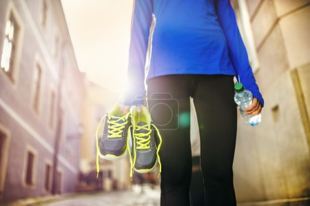 Female runner with shoes and bottle