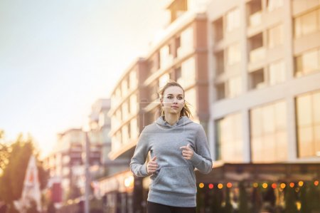 Photo pour Jeune coureuse à capuche fait du jogging dans la rue de la ville - image libre de droit