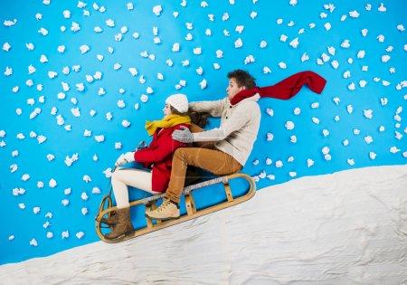 Young couple on sledge having fun