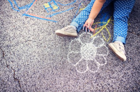 Photo pour Close up of little girl in canvas shoes drawing with chalks on the sidewalk - image libre de droit