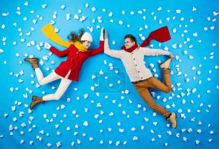 Photo pour Happy young couple in winter clothes having fun against the blue background with snowflakes - image libre de droit