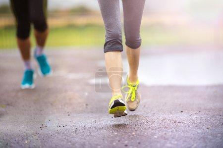 Couple running on asphalt sports field
