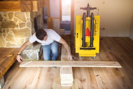 Hands measuring wood flooring