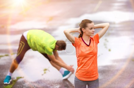 Photo for Young couple stretching after the run on asphalt in rainy weather - Royalty Free Image