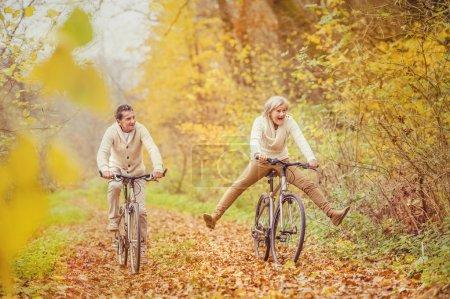 Photo pour Active seniors on bikes in autumn forest - image libre de droit