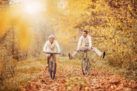 Photo for Active seniors on bikes in autumn forest - Royalty Free Image