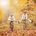 Active seniors on bikes in autumn forest...