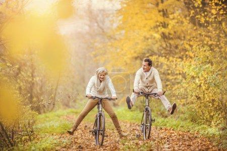 Photo pour Aînés actifs à vélo dans la forêt d'automne - image libre de droit