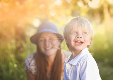 Photo for Mother and little son enjoying sunshine outside in nature - Royalty Free Image