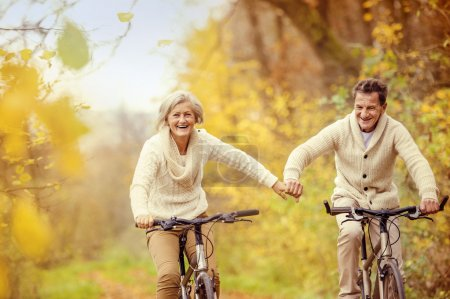 Photo for Active seniors on bikes in autumn nature - Royalty Free Image