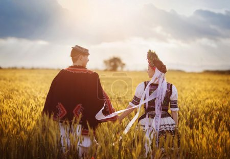 Photo for Rear view of Love couple holding hands in sunset field. They wearing traditional Eastern Europe folk costumes. - Royalty Free Image