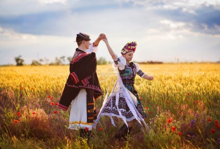 Photo for Love couple in sunset field. They wearing traditional Eastern Europe folk costumes. - Royalty Free Image