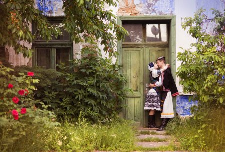 Photo for Love couple in traditional Eastern Europe folk costumes kissing on the porch - Royalty Free Image