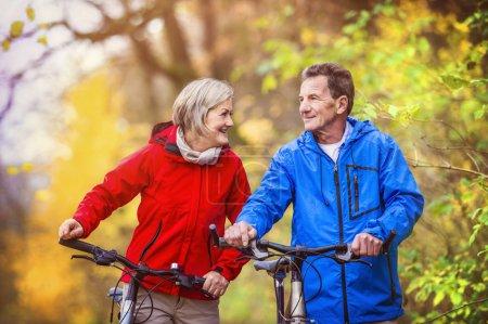 Active seniors having walk with bikes