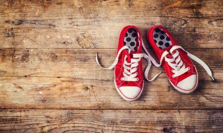 Photo pour Paire de baskets rouges sur le sol. Studio tourné sur un fond en bois . - image libre de droit