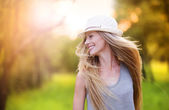 Woman in white hat laughing in sunny park