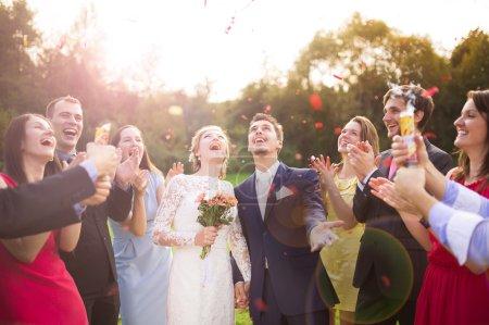 Photo pour Portrait d'un quart de longueur de couple nouvellement marié et leurs amis à la fête de mariage douché de confettis dans un parc vert ensoleillé - image libre de droit
