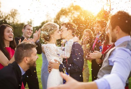 Young newlyweds kissing and enjoying romantic moment together at wedding reception outside, wedding guests
