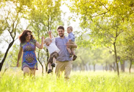 Photo pour Heureux jeune famille à pied et passer du temps ensemble à l'extérieur dans la nature verdoyante. - image libre de droit