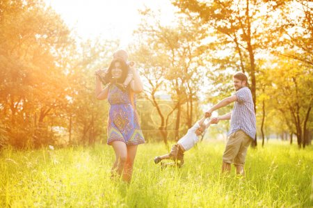 Photo pour Happy young family having fun together outside in green nature. - image libre de droit