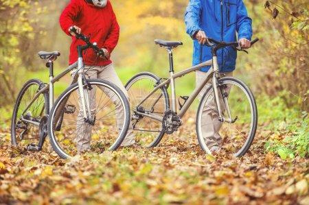 Photo pour Couple sénior actif se promenant à vélo en automne nature. détails des jambes et des vélos sur les feuilles tombées - image libre de droit