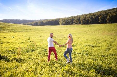 Photo pour Heureux jeune couple marcher et s'amuser à l'extérieur sur une prairie - image libre de droit