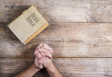 Hands of praying man with Bible