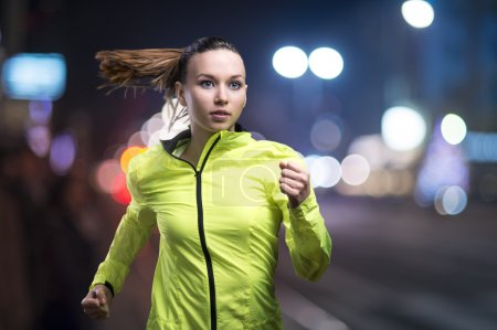 Photo for Young woman jogging at night in the city - Royalty Free Image