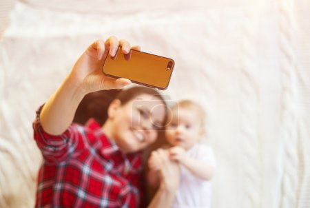 Photo for Cute little baby girl and her mother taking selfie on a blanket in a living room. - Royalty Free Image