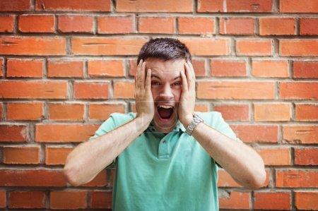 Photo pour Jeune homme beau faire des visages drôles sur un fond de mur de brique - image libre de droit