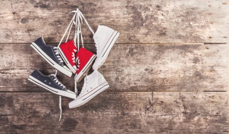 Photo for Three pairs of sports shoes hang on a nails on a wooden fence background - Royalty Free Image