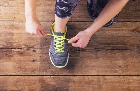 Runner tying her shoelaces.