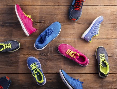 Photo for Various running shoes laid on a wooden floor background - Royalty Free Image