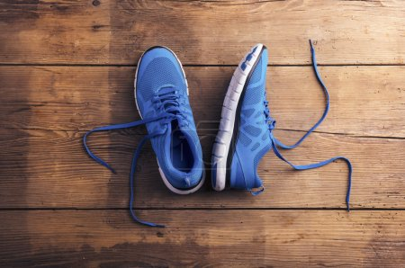 Photo pour Paire de chaussures de course bleues posées sur un fond de plancher en bois - image libre de droit