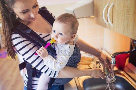 Photo pour Jeune mère laver la vaisselle avec sa petite fille qu'elle a dans un porte-bébé - image libre de droit