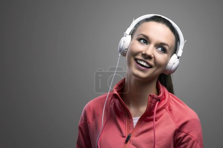 Photo for Young runner listening music. Studio shot on a gray background. - Royalty Free Image