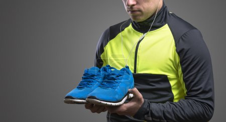 Photo for Young runner holding blue running shoes. Studio shot on gray background. - Royalty Free Image