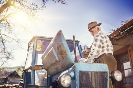 Photo for Senior man at the farm repairing an old tractor - Royalty Free Image