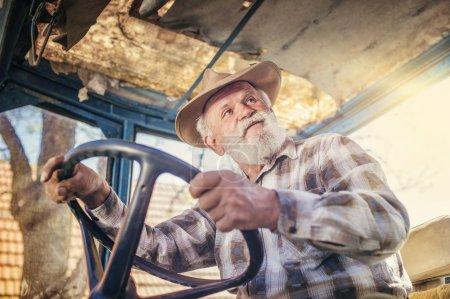 Foto de Hombre mayor en la granja conduciendo un viejo tractor - Imagen libre de derechos