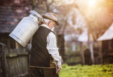 Farmer carrying milk kettle