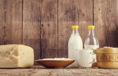 Variety of dairy products laid on a wooden table b...